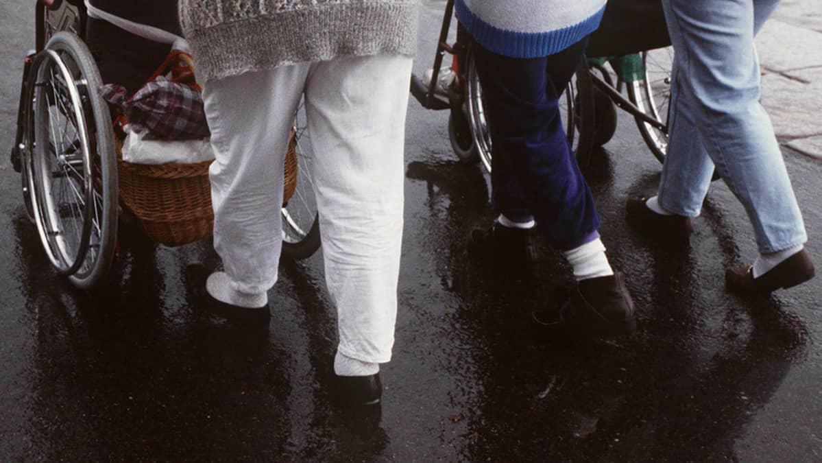 Hoitajat työntävät liikuntavammaisia pyörätuoleissa.