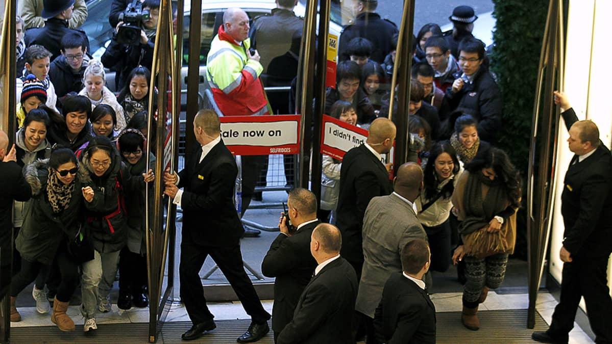 Ihmiset tungeksivat sisään Selfridgen tavarataloon sen avattua ovensa ja aloitettua alennusmyyntinsä.