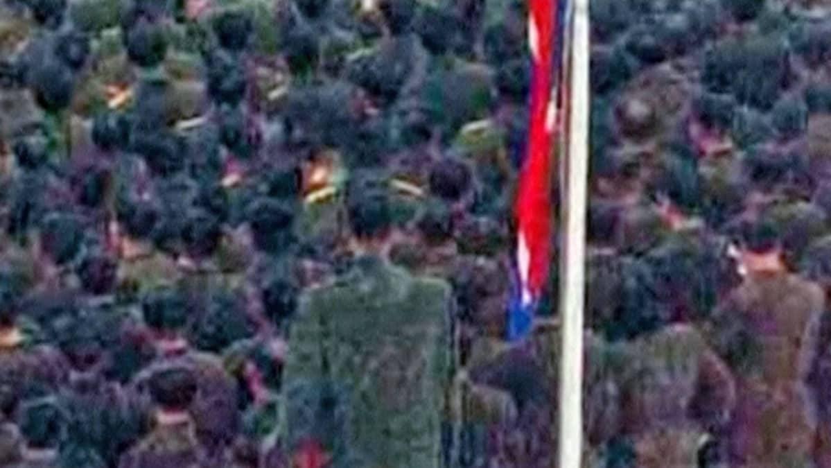 Sotilasrivissä seisova jättiläismäinen mies on herättänyt verkossa valtaisaa spekulaatiota henkilöllisyydestä.