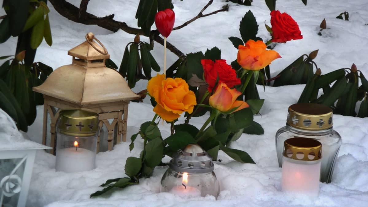 Ruusuja ja hautakynttilöitä lumisella hautausmaalla.