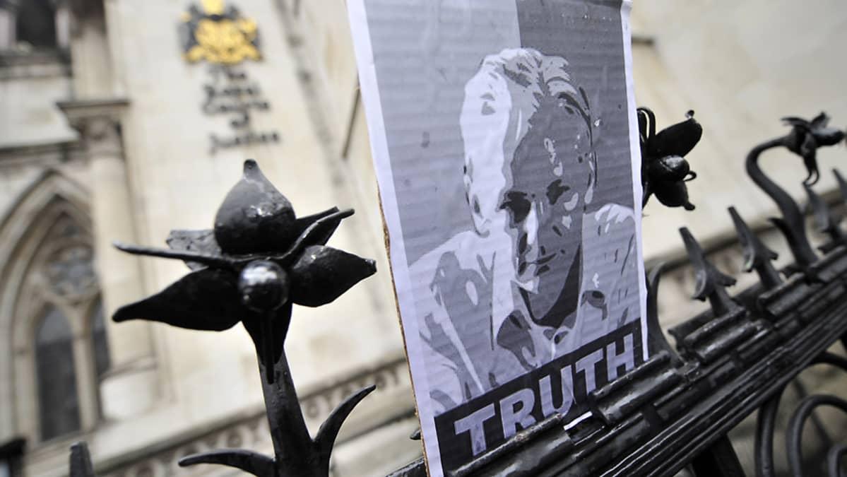 Julian Assangen mustavalkoinen kopiokuva on nostettu Lontoon korkeimman oikeuden rauta-aidan päälle.