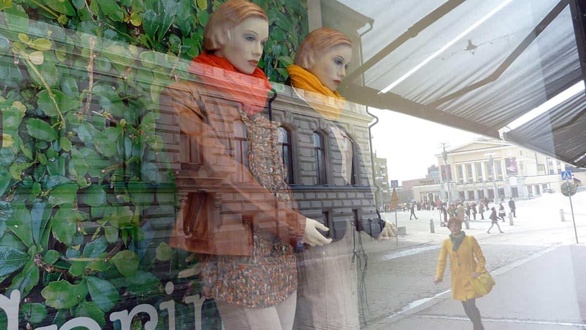 Näyteikkunassa kaksi mallinukkea puettuna värikkäisiin vaatteisiin
