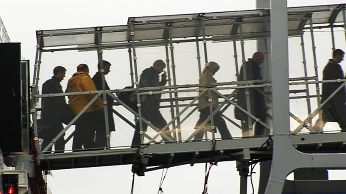Matkustajat poistuvat laivasta jalankulkusiltaa myöten
