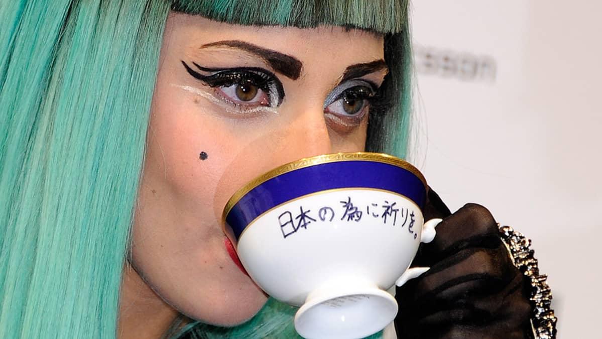 Lady Gaga juomassa huutokaupassa myydystä teekupista lehdistötilaisuudessa.