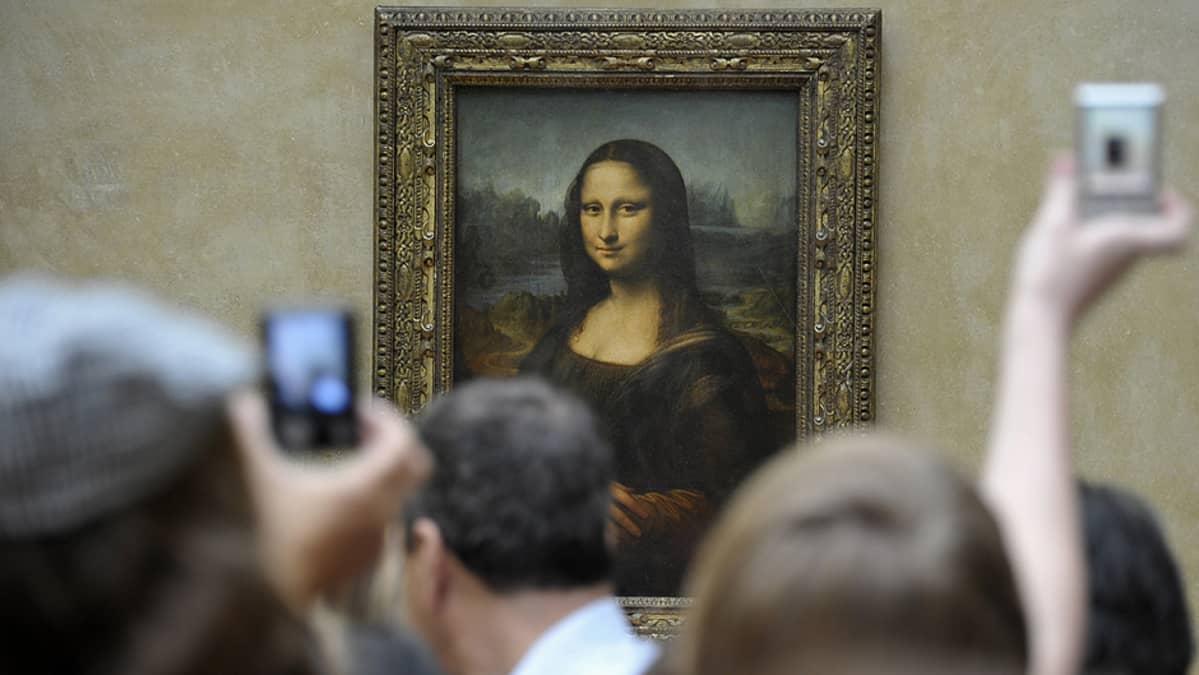Ihmiset tungeksivat Mona Lisan edustalla Louvren taidemuseossa.