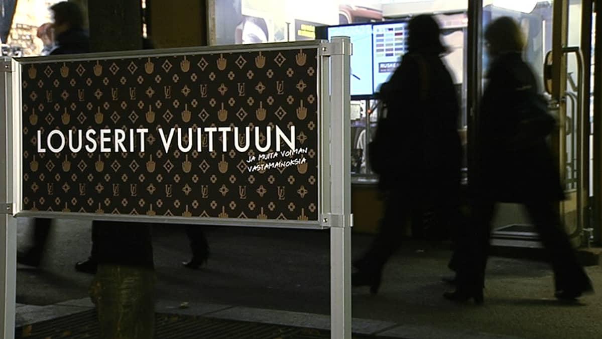 Voima-lehden vastamainosnäyttelyn kyltti näyttelytilan edustalla Helsingin Kampissa.