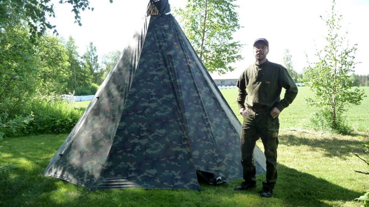 Anssi Romo seisoo telttakodan edessä.