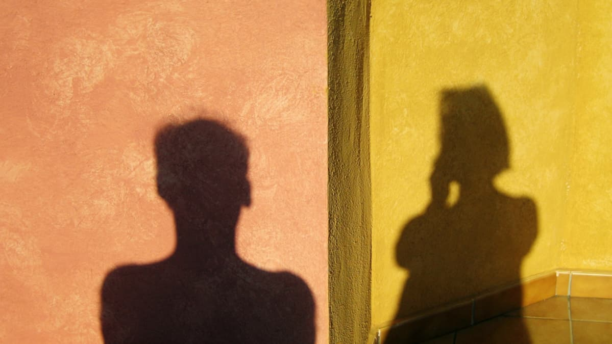 Miehen ja naisen varjot vierekkäisillä seinillä.