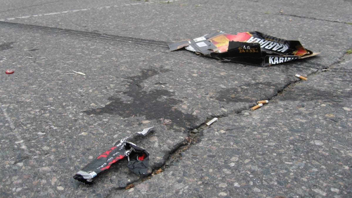 Roskia ja auton renkaan jälkiä asfaltissa