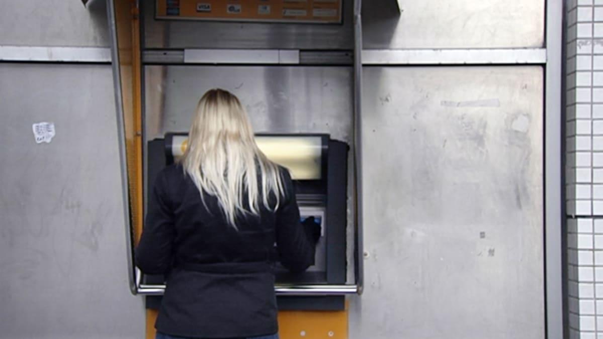 Nainen nostaa rahaa pankkiautomaatilla.