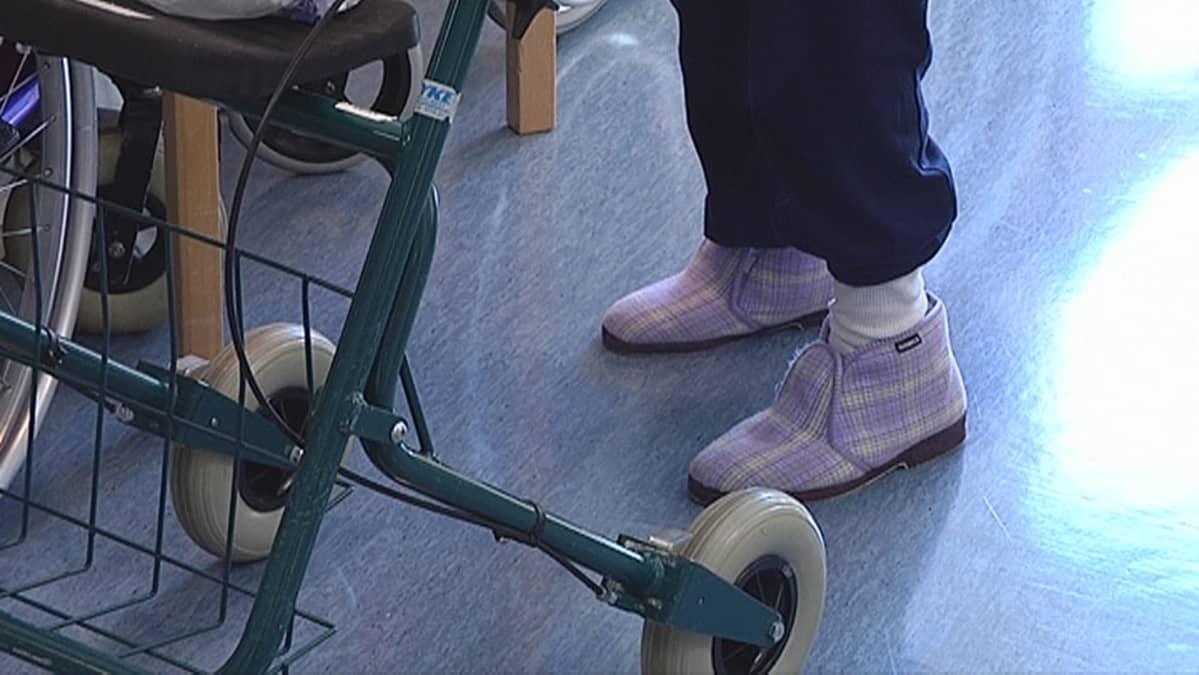 Vanhuksen jalat ja rollaattori sairaalassa.