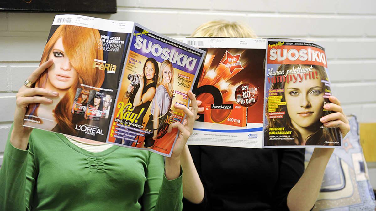 Kaksi henkilöä lukemassa Suosikki-lehteä.