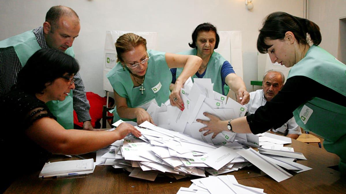 Viranomaiset setvivät pinoa äänestyslappuja.