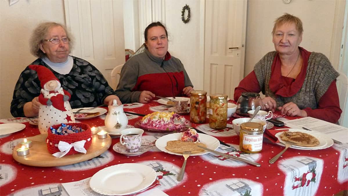 Vasemmalta Raija Juvonen, Irme Talberg ja Irina Sokolova joulupöydän äärellä
