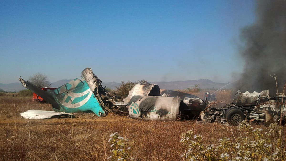 Lentokoneen savuava, pahoin vahingoittunut runko.