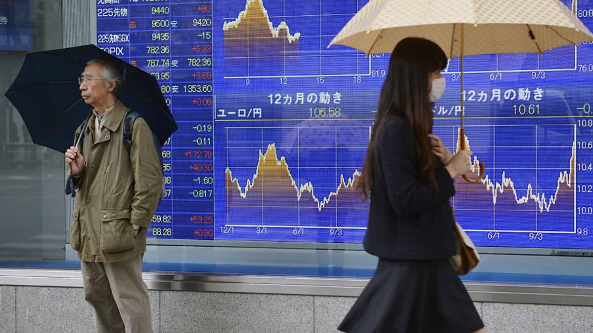 Sateen varjoja kannattelevat mies ja nainen pörssikursseja osoittavan ison näytön edessä.