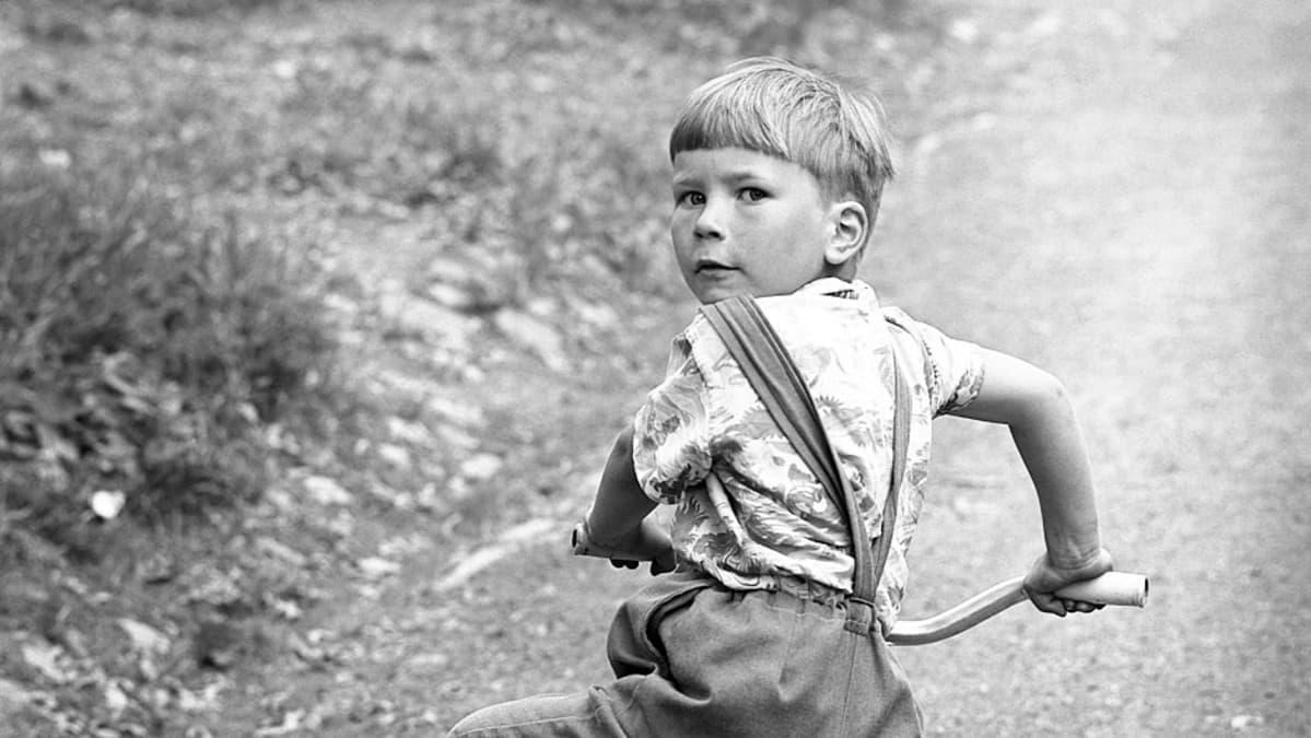 Nuori poika fillaroimassa. Mustavalkokuva 60-luvulta.