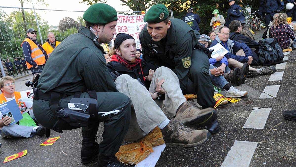 Poliisi kantaa pois mielenosoittajia.