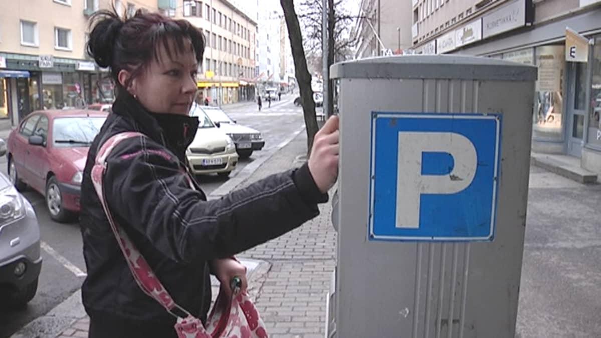 Nainen maksaa pysäköintimaksua