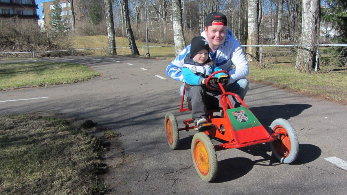 Poika istuu polkuauton kyydissä