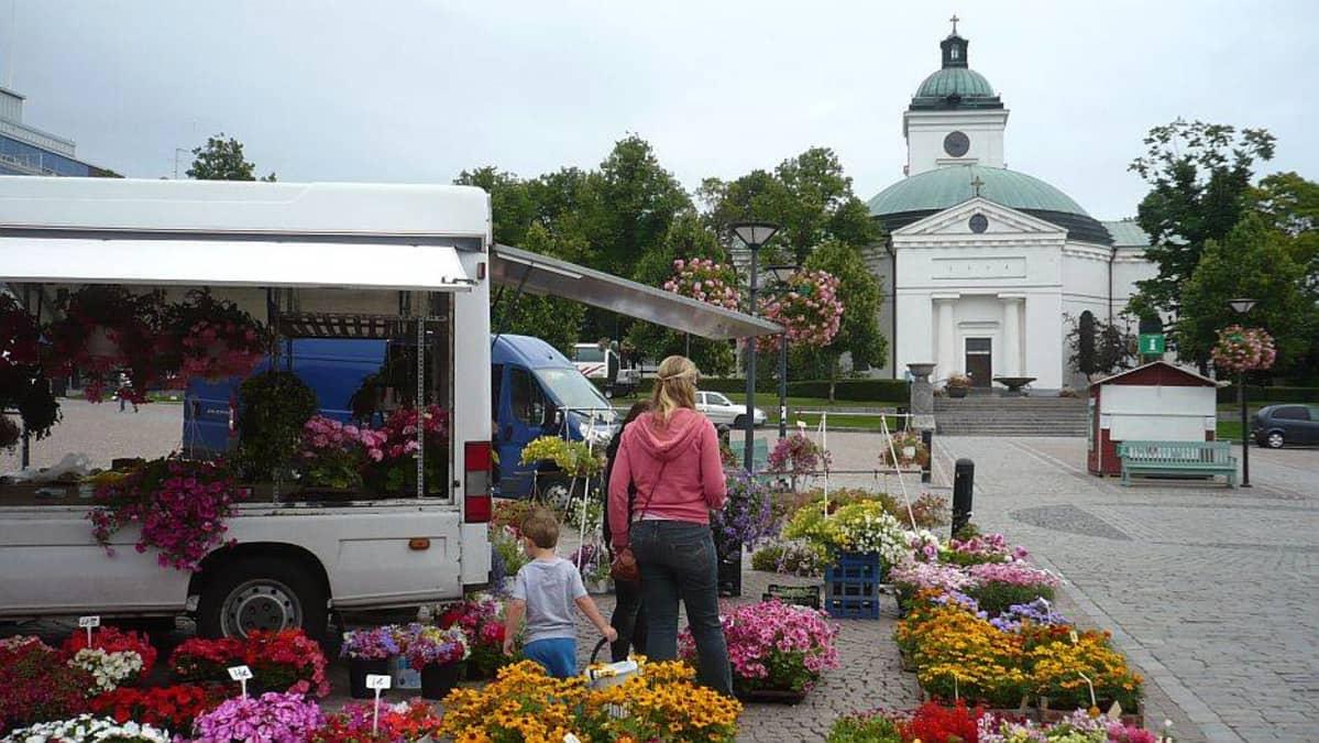Kukkienmyyjä Hämeenlinnan torilla, taustalla kirkko