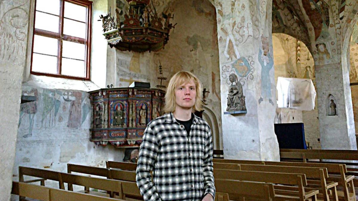 Jyrki Nissi Hattula Pyhän Ristin keskiaikaisessa kirkossa, seinillä maalauksia ja patsaita.