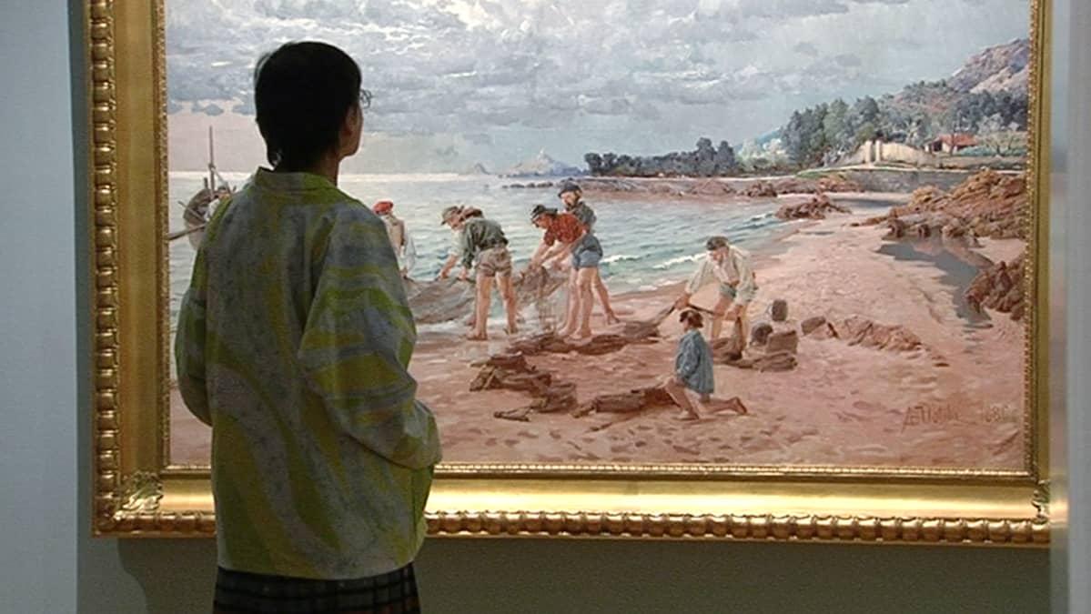 Näyttelyvieras katselemassa August Uotilan maalausta Amos Andersonin taidemuseossa.