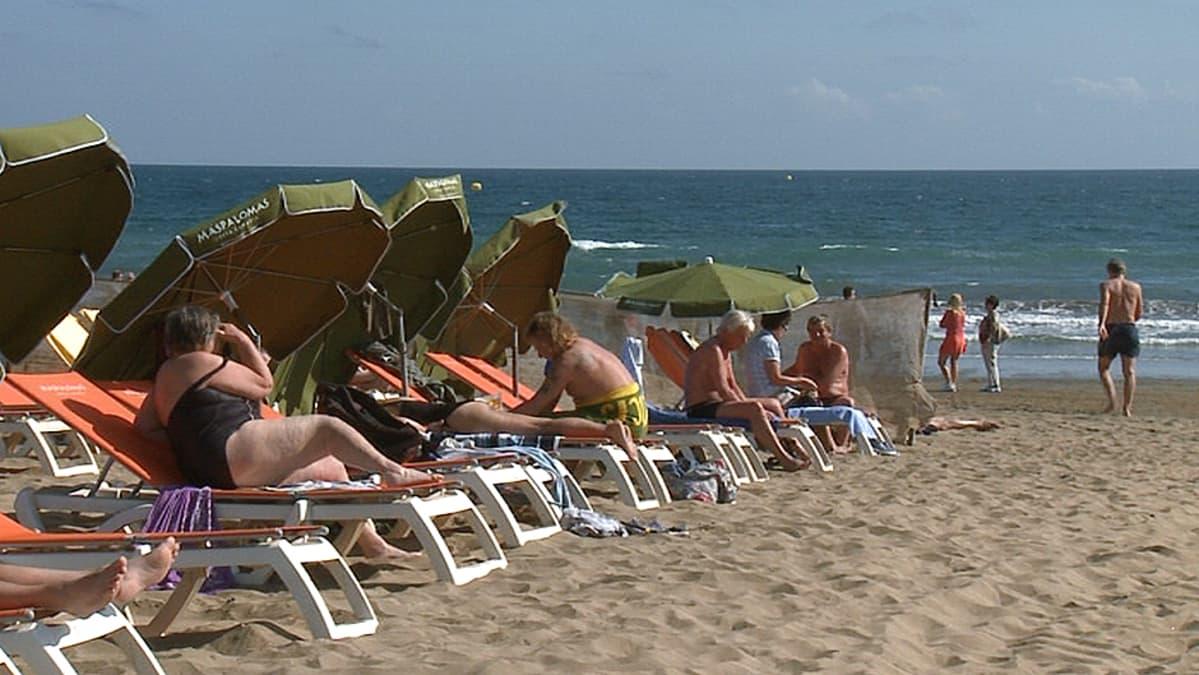 Turisteja uimarannalla Playa del Inglesissä Kanariansaarilla.