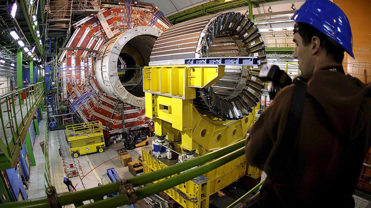 Valokuvaaja CERN:in Genevessä sijaitsevan LHC-hiukkastörmäyttimen CMS-hiukkastunnistimen vierellä.