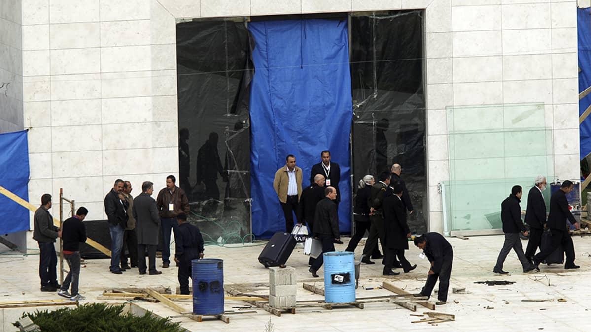 Palestiinalaisia viranomaisia sekä todennäköisesti Jasser Arafatin ruumista tutkivia asiantuntijoita tämän mausoleumin ulkopuolella.
