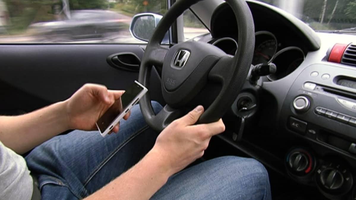 Mies ajaa autoa ja käyttää älypuhelinta.