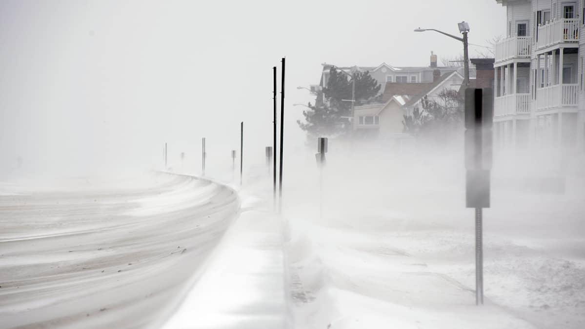 Tuuli puhaltaa lunta rannalta sisämaahan.