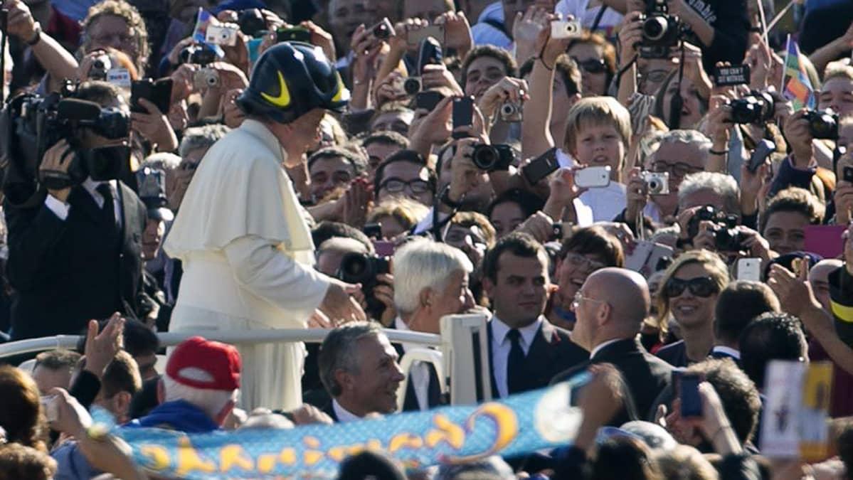 Paavi Franciscus käyttää palomiehen kypärää tavatessaan kansaa Pyhän Pietarin aukiolla Vatikaanissa.