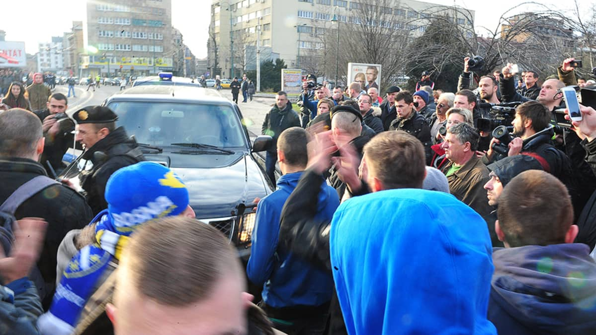 Ihmiset tukkivat poliisiautojen kulun kadulla.