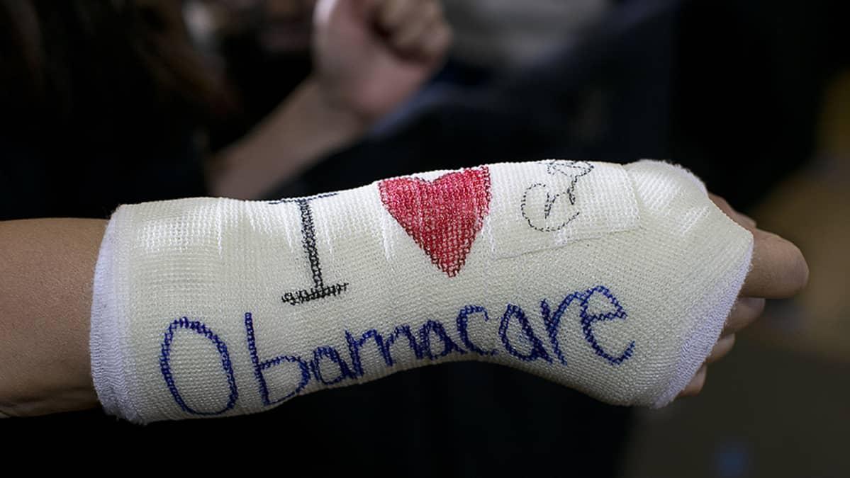 Presidentti Barack Obaman tukija on kirjoittanut kipsiinsä rakastavansa tämän sairausvakuutusmuutosta.