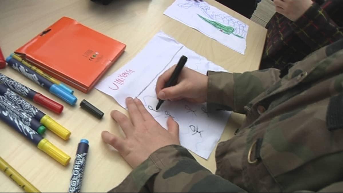 Koululainen piirtää.