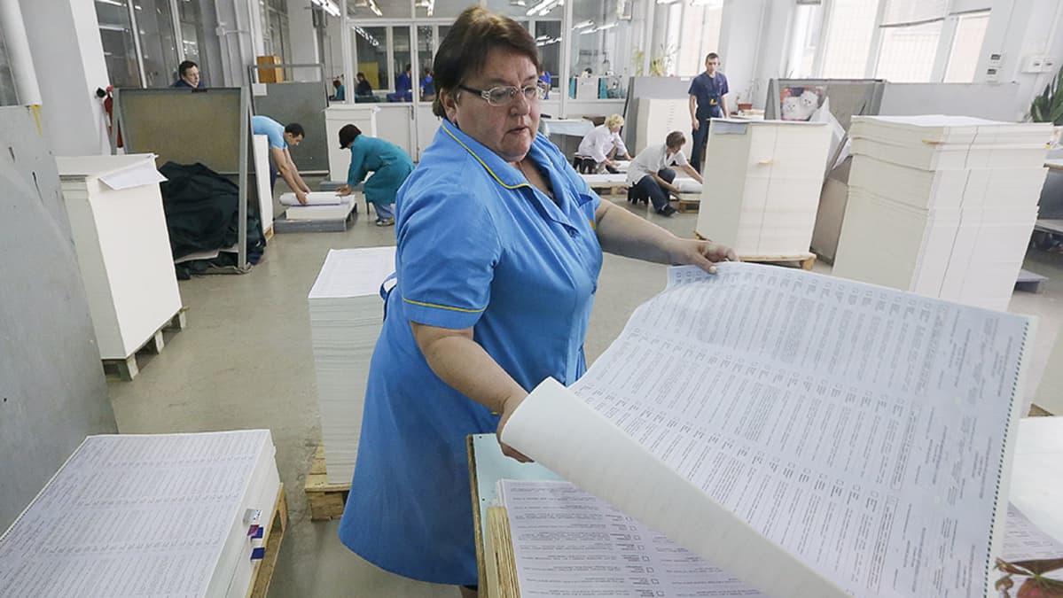 Painotalon työntekijät pinoavat vastapainettuja äänestyslistoja.