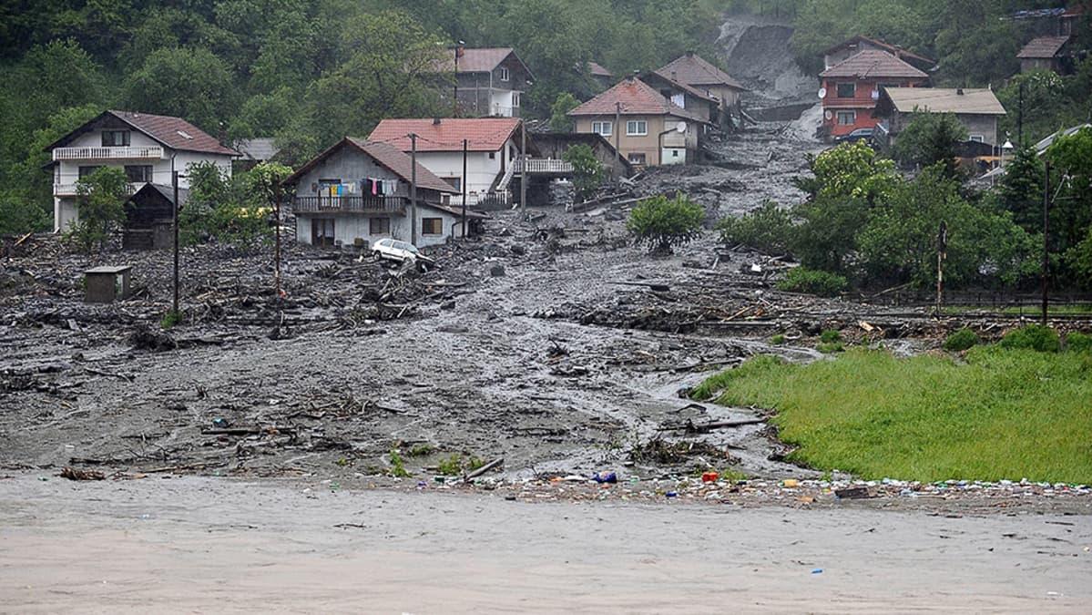 Tulvavesien aiheuttama maanvyöry kylän keskellä.