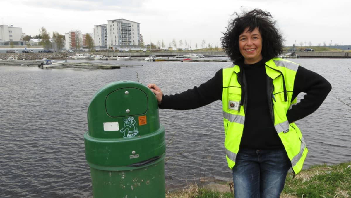 Kemin kaupungin kenttäpuutarhuri Katri Lassila esittelee koirakäymälää, eli koirankakkapusseja varten kaupungille tuotua roska-astiaa.