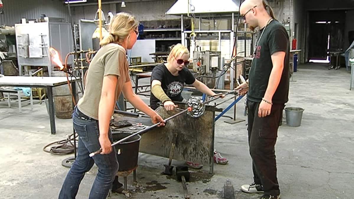 Nuutajärven lasikoulun opiskelijoita työstämässä lasia.