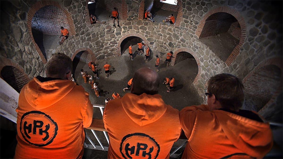 Oranssihuppariset miehet seisovat ylhäällä ja katsovat alapuolellaan olevia pelaajia.