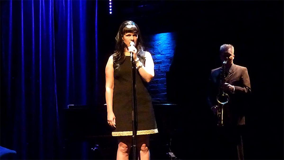 Nainen laulaa ja mies soittaa taustalla saksofonia.