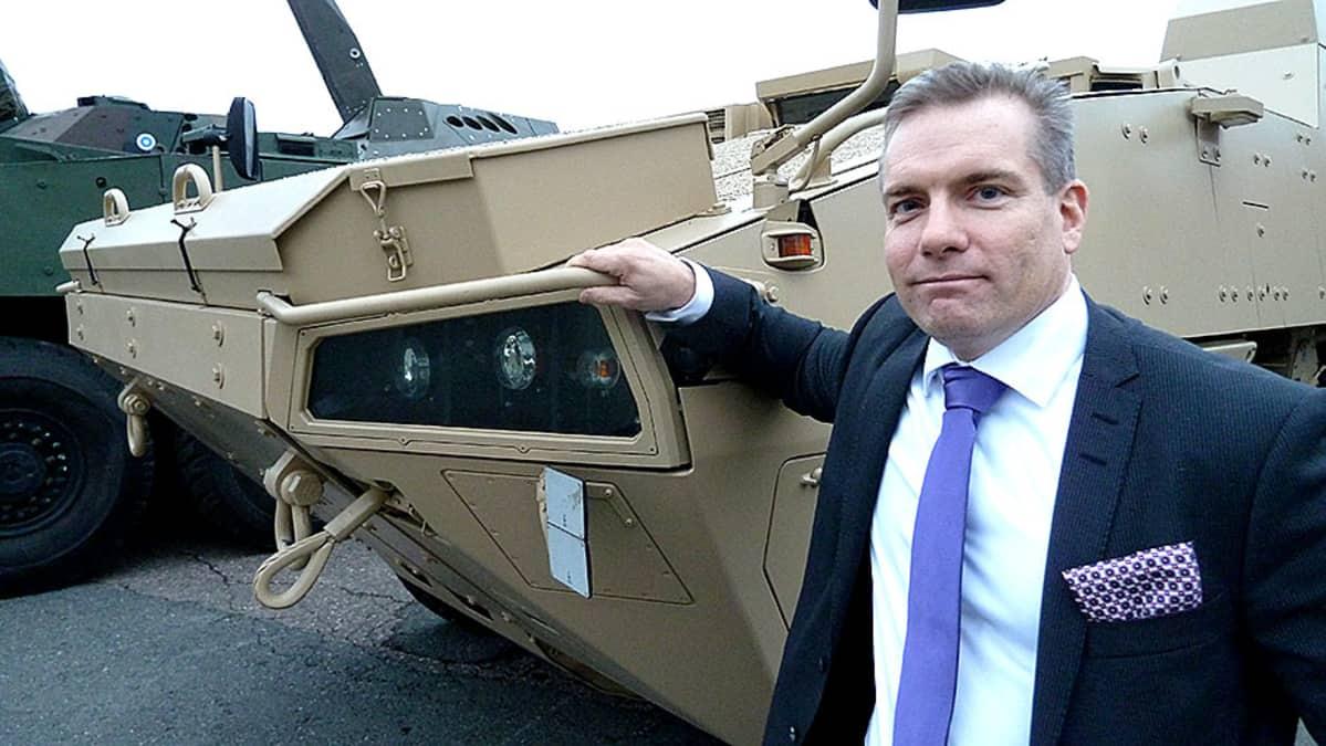 Mies seisoo panssariajoneuvon edessä