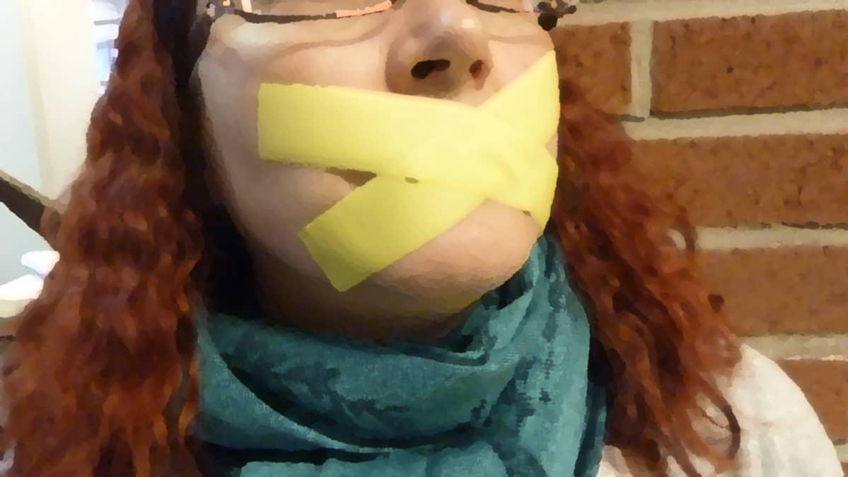 Punahiuksisen naisen suu on teipattu kiinni.