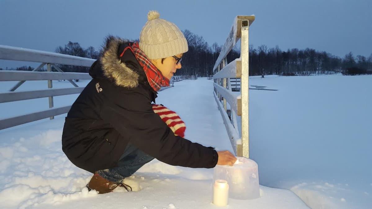 Kirsi Niikkonen sytyttää jouluvaloja Kuusamon kirkkosaareen johtavalla sillalla.