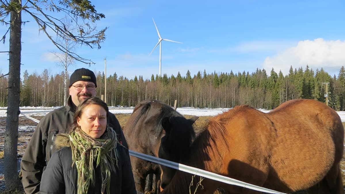 Harri Tryyki ja Katja Äijälä kotipihallaan Tervolassa. Taustalla näkyy tuulivoimala.
