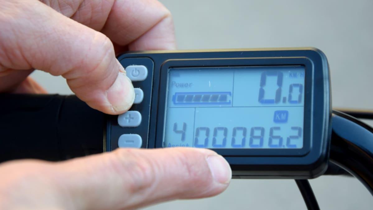 Mies osoittaa sormella sähköpolkupyörän mittaria
