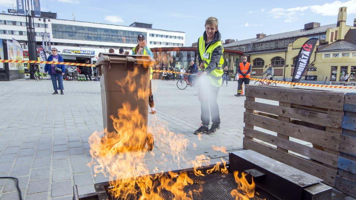 Koululainen sammuttaa tulipaloa pelastustaitokilpailussa.