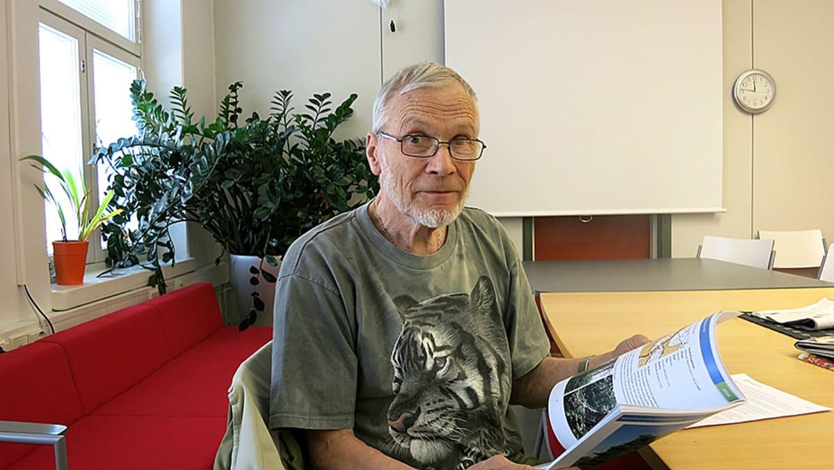 Juhani Kuusinen pitää kirjaa kädessään