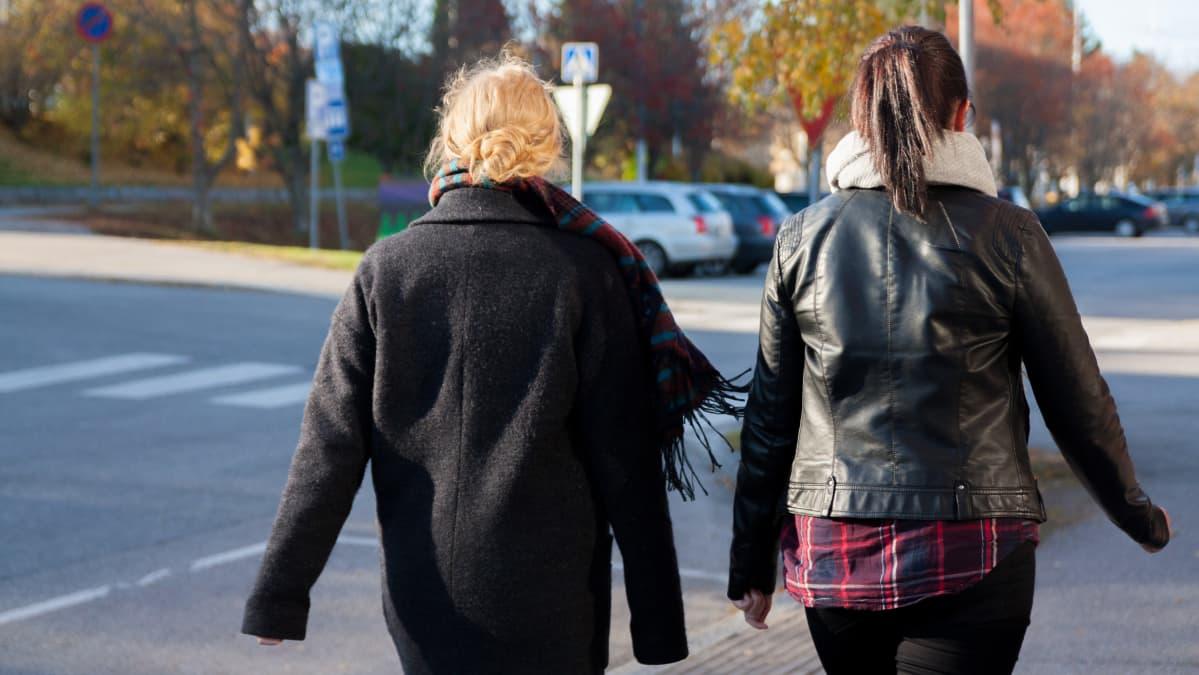 Kaksi tummiin pukeutunutta naista kävelee kadulla.